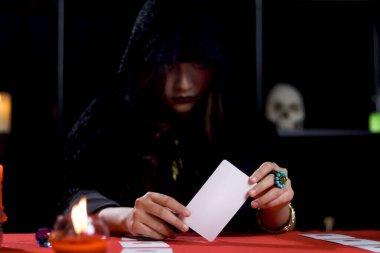 Siyah başlıklı kara cadı elinde sihirli kart, gizemli güzel kadın falcı geleceği kartla okuyor, korkutucu Cadılar Bayramı konsepti..