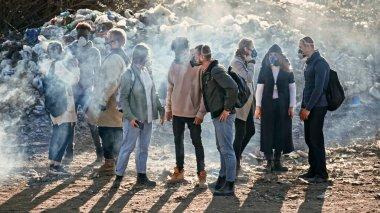 Gaz Maskeleri 'ndeki Genç Gönüllüler Çöp Döküntüsü' nde dururken Çevreye Bakım Yapıyor. Eylemciler Dünya Çapındaki Kirlilik Sorununu Tartışıyor.