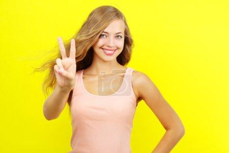 Photo pour Adolescente montrant le signe de la victoire sur fond jaune - image libre de droit