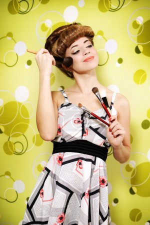 Retro style. Beautiful girl with makeup brushes