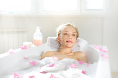 Attractive girl relaxing in bath on light backgrou...