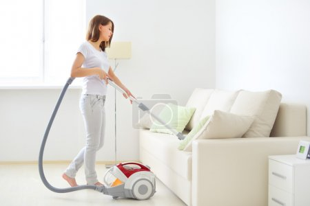 Attractive girl with vacuum cleaner on light backg...