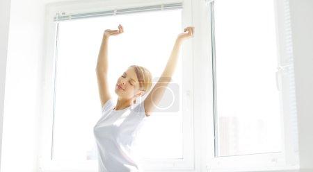 Photo pour Jeune fille qui s'étend dans la matinée. jeune fille se réveiller le matin. fenêtre de l'arrière-plan - image libre de droit