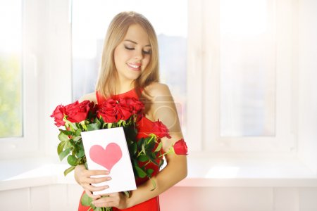 Beautiful girl with bouquet of red roses