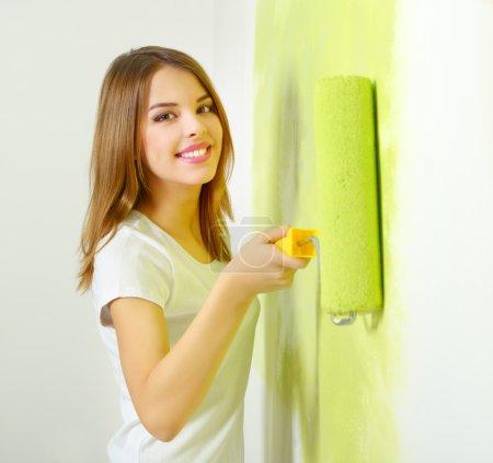 Photo pour Belle fille peignant un mur. fond clair - image libre de droit