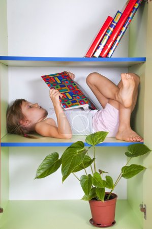 child reading a book in a bookcase