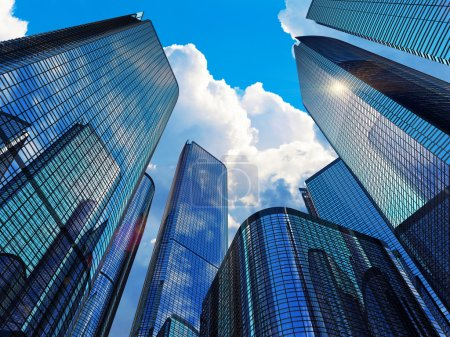 Photo for Downtown corporate business district architecture concept: glass reflective office buildings skyscrapers against blue sky with clouds and sun light - Royalty Free Image