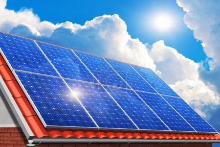 Foto de Tecnología creativa de generación de energía solar, energía alternativa y protección del medio ambiente ecología concepto de negocio: grupo de paneles de baterías solares en casa roja, casa o techo de baldosas contra el cielo azul con luz solar y nubes blancas - Imagen libre de derechos