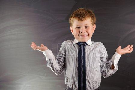 Cute boy against blackboard