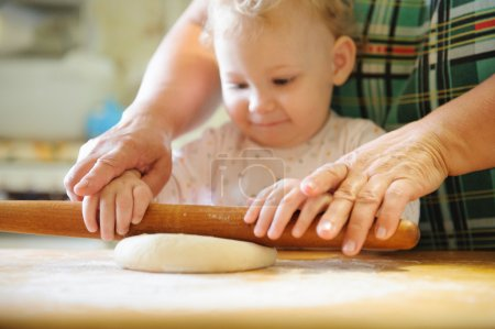 Photo for Baby girl rolling dough with her mother - Royalty Free Image