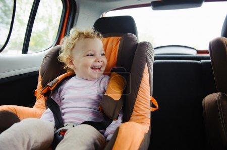 Photo pour Enfant heureux souriant dans siège auto - image libre de droit