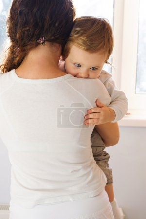 Mother holding her baby near window