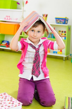 Photo for Cute little girl making a roof from book at home - Royalty Free Image