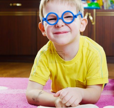 Photo for Funy little boy in glasses lying on floor - Royalty Free Image