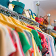 Variety of clothes hanging on rack in boutique...