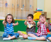 Excited children holding thumbs up