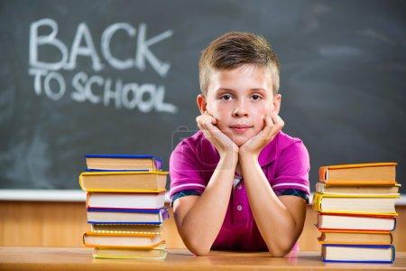 Photo pour Élève mignon avec une pile de livres dans la salle de classe - image libre de droit