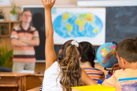 Photo pour Écolière levant la main à la leçon de géographie. Vue arrière - image libre de droit