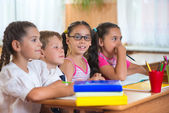 Four diligent pupils studying at classroom