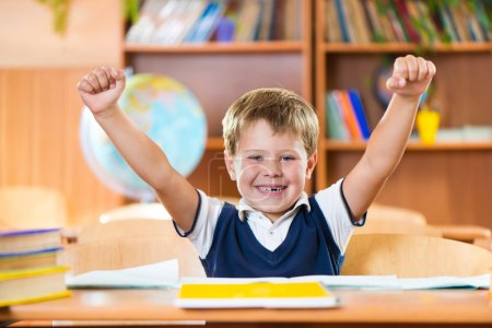 Successful schoolboy with hands up sitting at desk