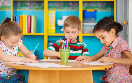 Three preschool children drawing at daycare