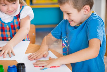 Photo pour Enfants d'âge préscolaire mignons peinture avec leurs palmiers au jardin d'enfants - image libre de droit