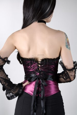 Rear view of a woman in purple corset with lace overlay