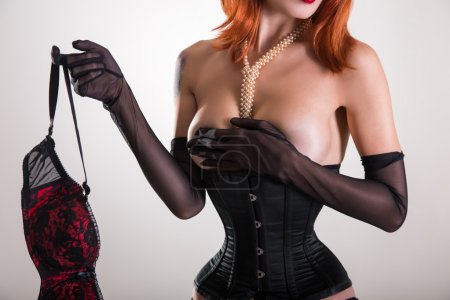Glamorous pinup woman in corset holding red bra
