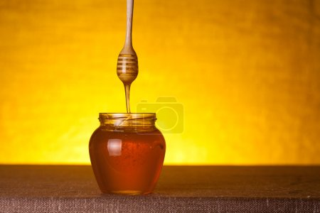 Honey jar with wooden dipper and flowing honey