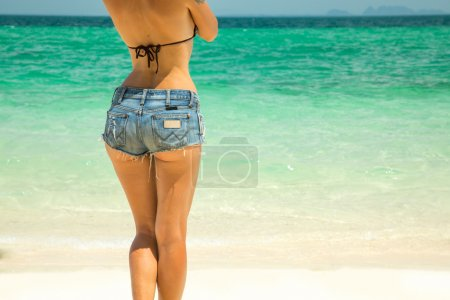Photo for Young beautiful woman in denim shorts sunbathing on the beach - Royalty Free Image