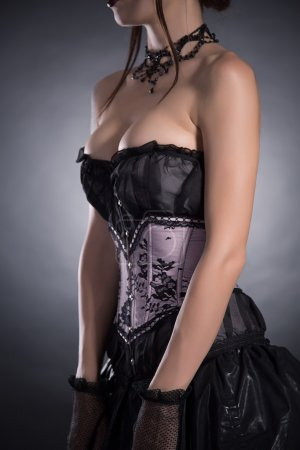 Photo for Close-up shot of a busty woman in elegant corset with floral pattern, studio shot - Royalty Free Image