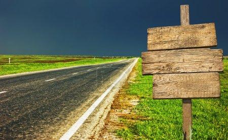 Photo pour Vieux panneau en bois sur la route de campagne - image libre de droit