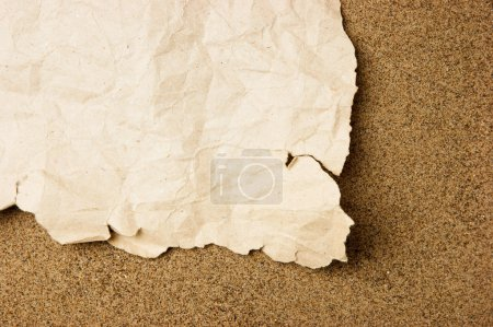 scrap of old torn paper on a sandy beach