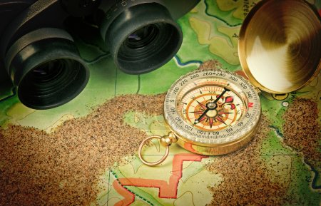 Photo for Binoculars and a compass on the map with sand - Royalty Free Image