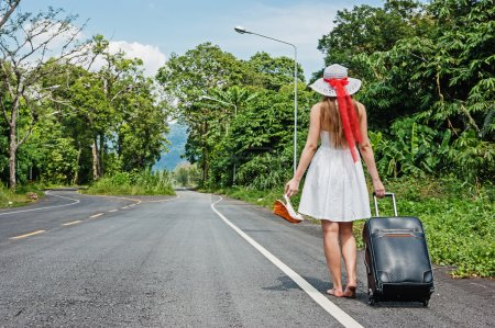 Photo pour Jeune fille marche sur la route avec une valise - image libre de droit
