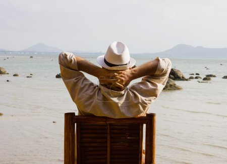 Photo for Man sitting on a chair and looks at the sea holding his hands on his neck, back view - Royalty Free Image