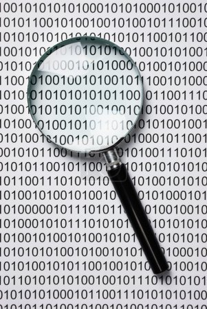magnifying glass on a binary code