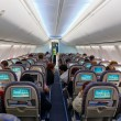 Passengers sitting on their chairs in airplane cab...