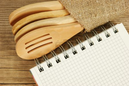 wooden spoon and notebook on old wooden table