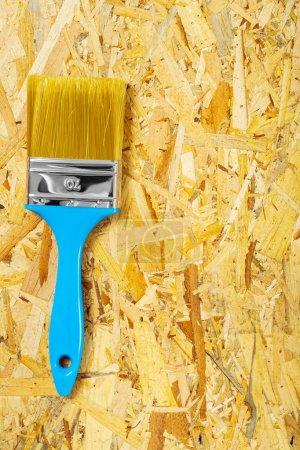 single paintbrush on plywood