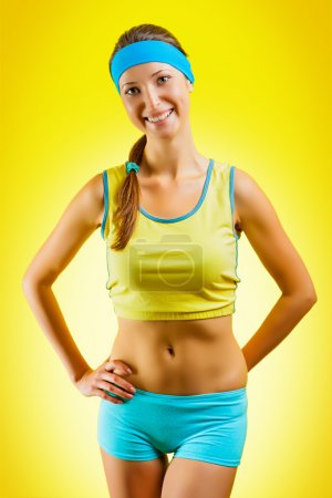 A sporty girl on yellow background