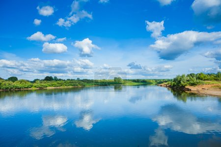Wide river with reflection and green bush on coasts and blue cloudy sky
