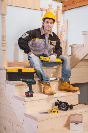 Contractor sitting on steps of wooden ladder with tools