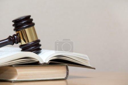 Photo pour Marteau en bois et livres sur table en bois - image libre de droit