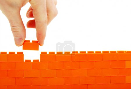 Photo for Completing the wall on a white background,man hand putting last brick to toy wall - Royalty Free Image