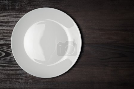 Photo for White plate on the wooden brown table - Royalty Free Image