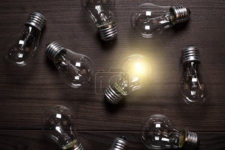 Photo for Glowing bulb over wooden background uniqueness concept - Royalty Free Image