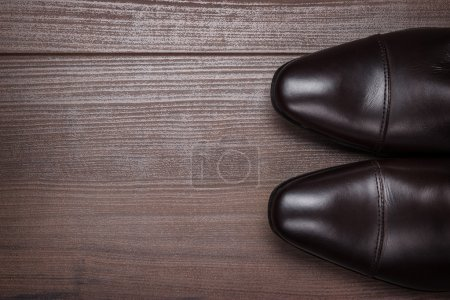 Photo for Man in brown shoes standing on the wooden floor background - Royalty Free Image
