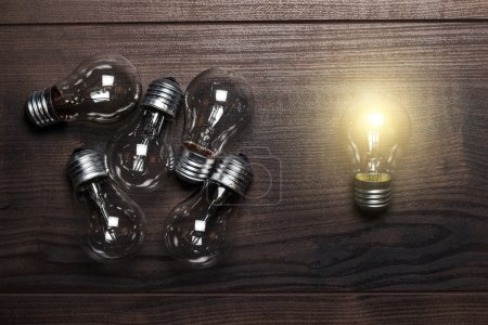 Bulbs uniqueness concept on wooden background