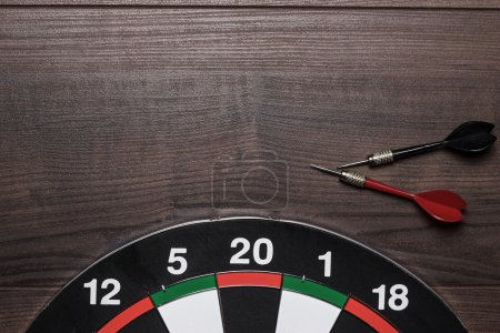 Target and two darts on brown wooden table